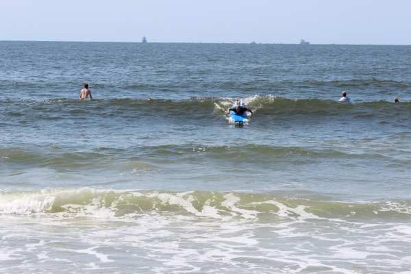 Here I am paddling to build momentum so that I can ride the wave that's building behind me.